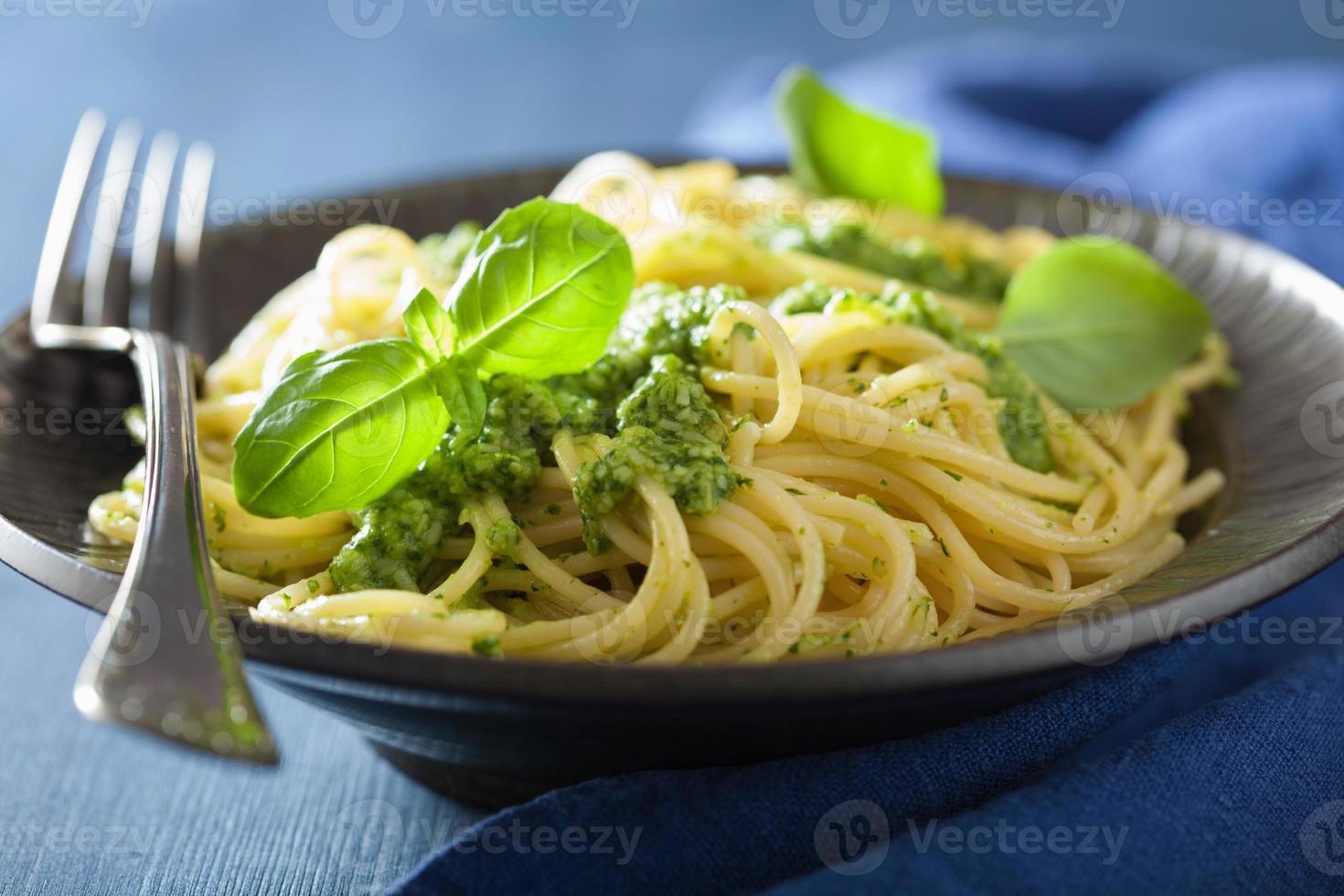 pasta de espagueti con salsa de pesto sobre azul foto