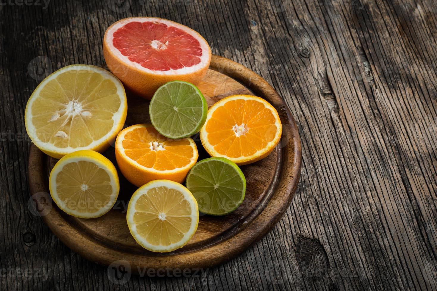 Halves of citrus fruits on wooden background photo