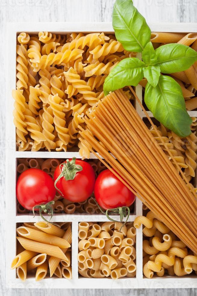 various raw wholegrain pasta in white wooden box photo