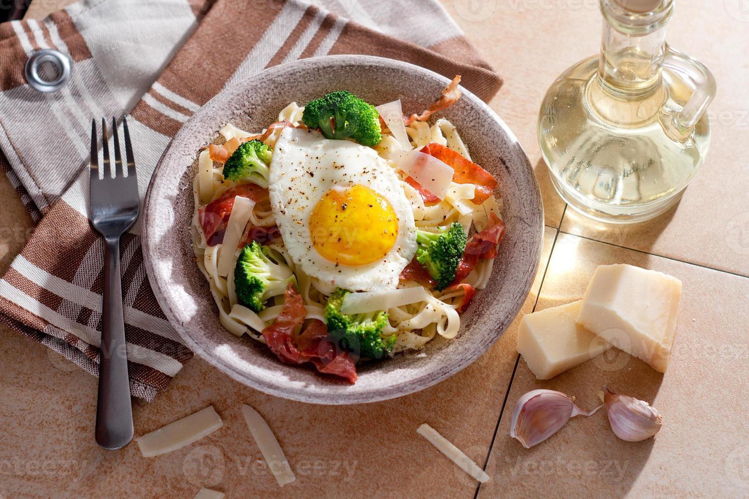 Tagliatelle pasta with broccoli, prosciutto and fried egg. photo