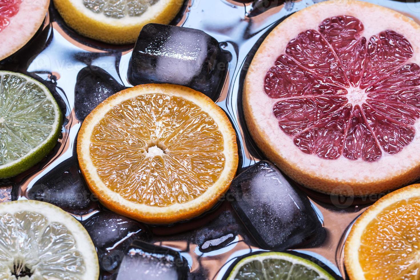 Sliced citrus fruits lemon, lime, orange, grapefruit with ice ov photo