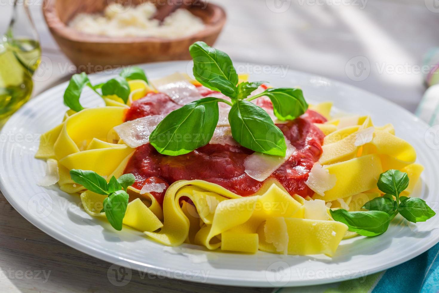 Homemade pappardelle pasta with tomato sauce and basil photo
