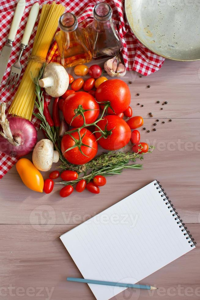 Spices, pasta and vegetables around notebook. photo