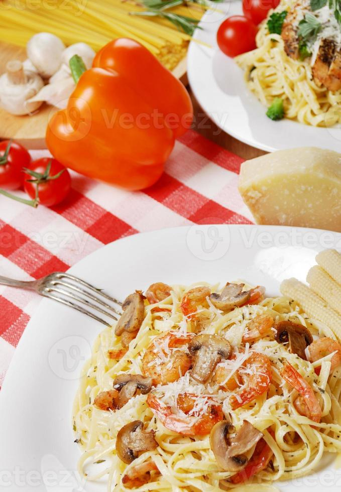 pasta con camarones y champiñones en la mesa de madera foto