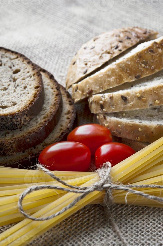 Dry pasta and tomatoes with sliced bread on sack background photo