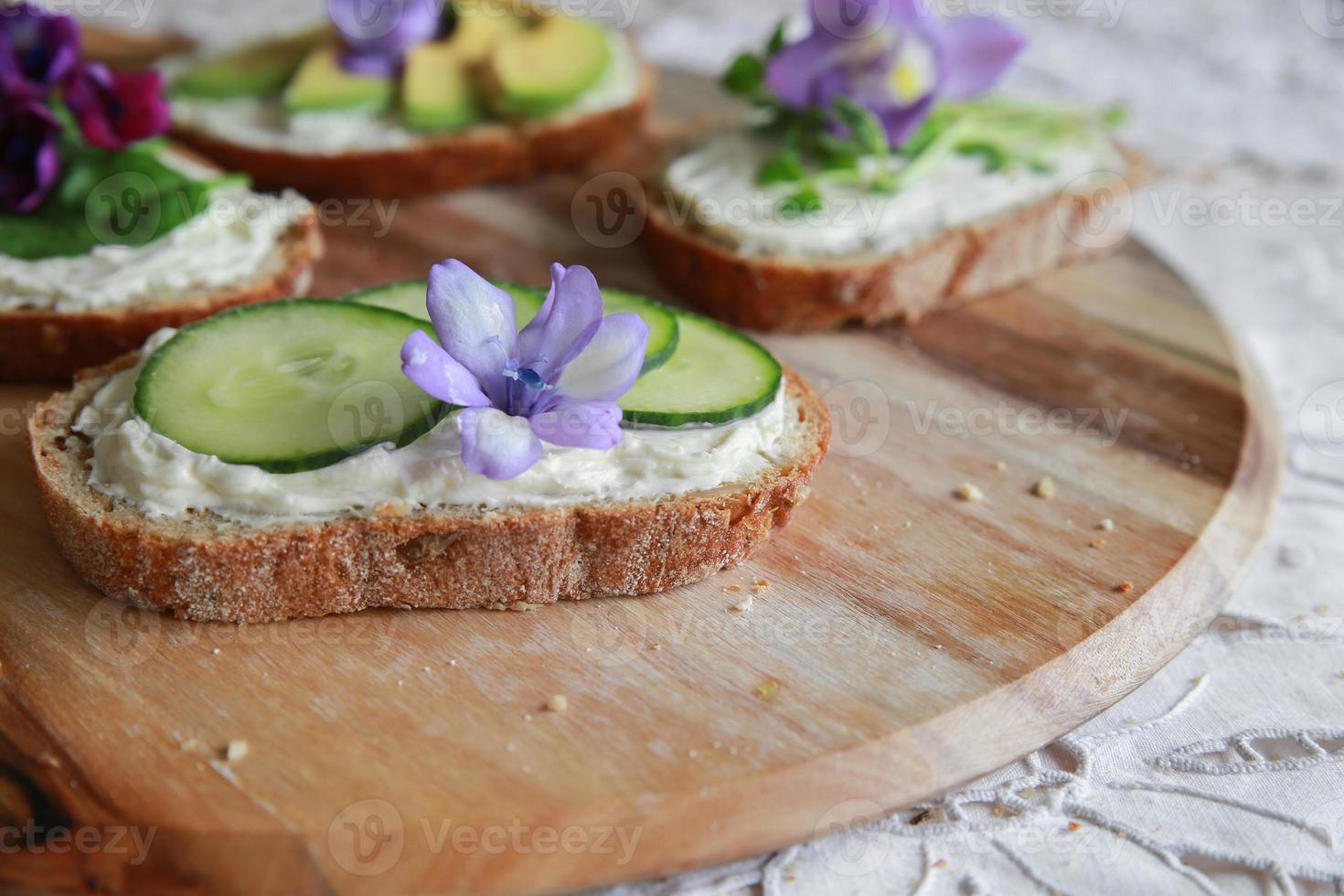 sanduíches de rosto aberto de fermento verde com flores comestíveis roxas foto