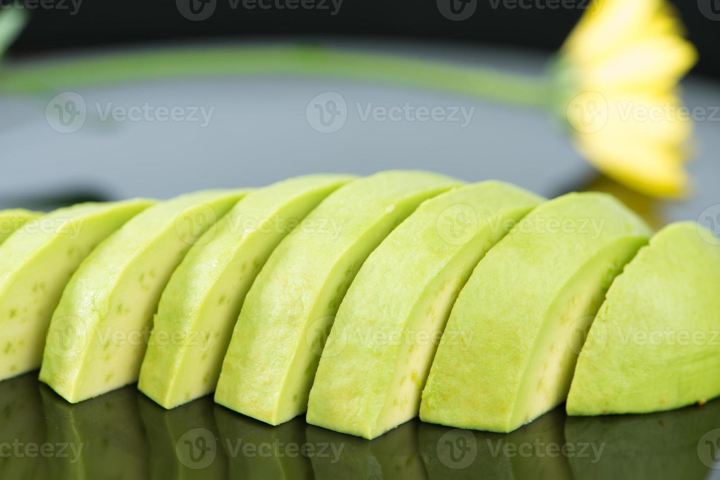 Slice avocado fruit on black dish photo