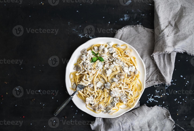 espaguete de macarrão com molho cremoso de cogumelos e manjericão em branco foto
