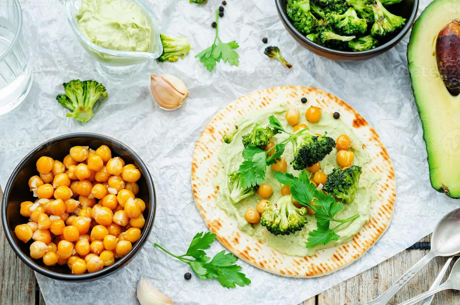 vegan tortilla with roasted broccoli and chickpeas and avocado sauce photo