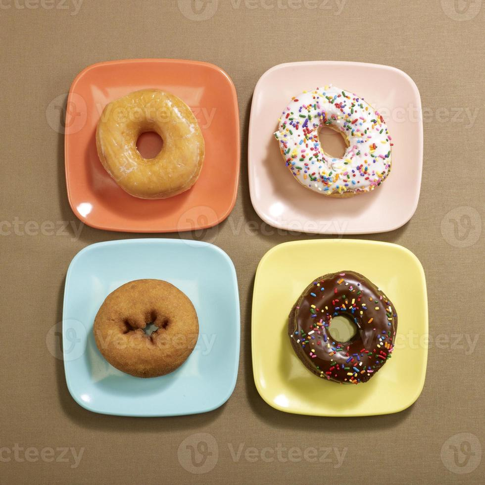 Overhead of Four Doughnuts on sqaure plates photo