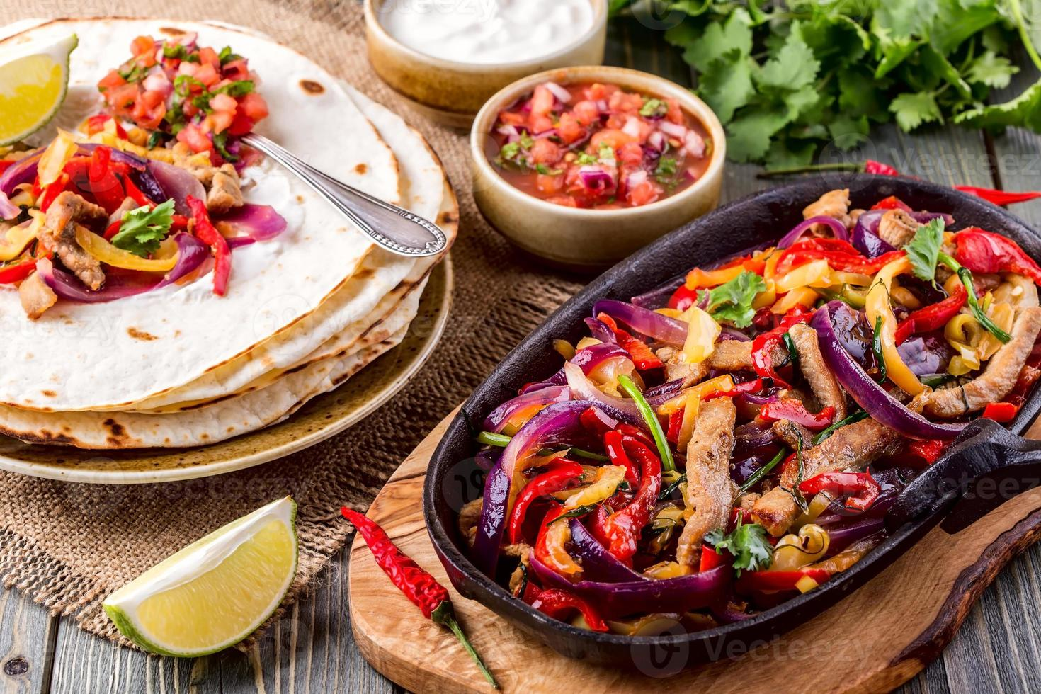 Pork fajitas with onions and colored pepper, served with tortill photo