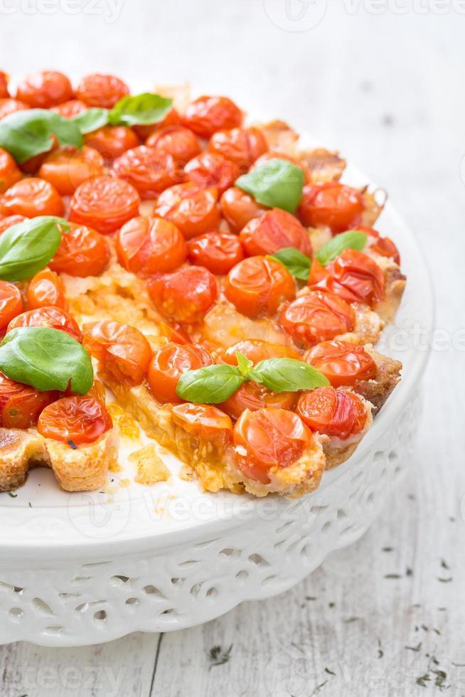 versgebakken taart met cherrytomaatjes op wit foto