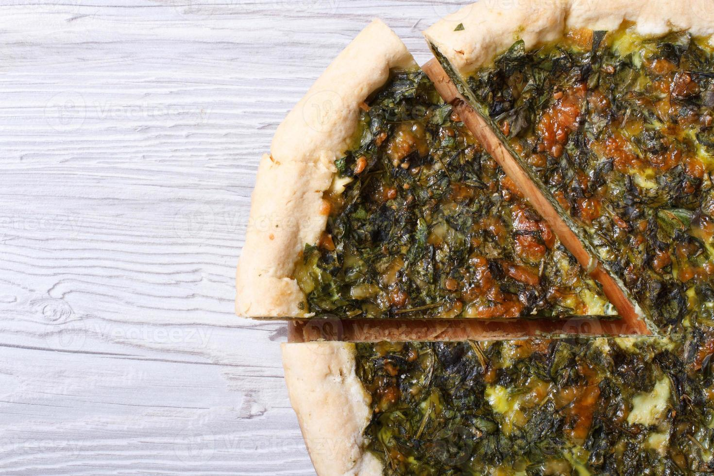 useful pie with spinach, cheese on wooden table close-up photo