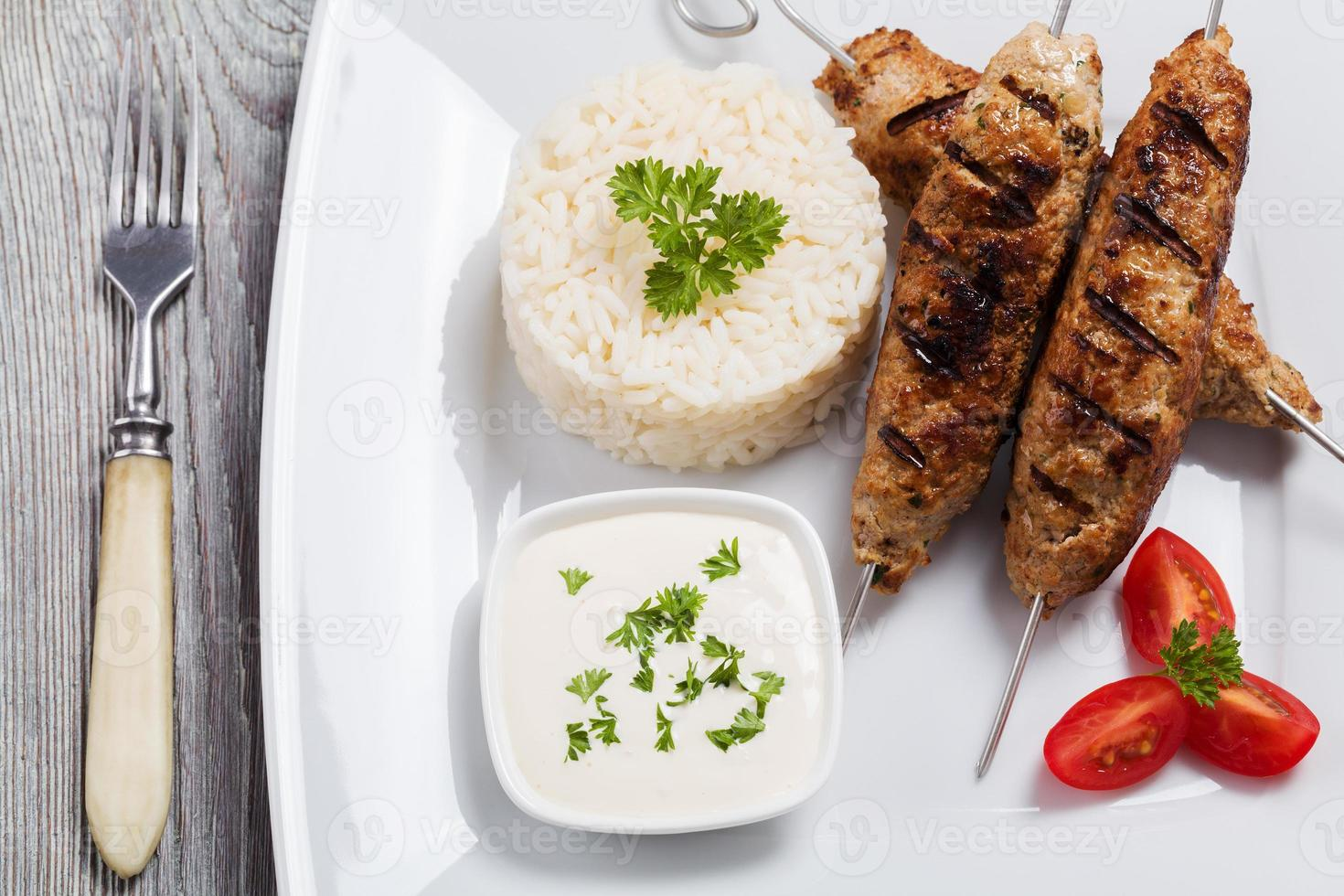 Barbecued kofta - kebeb with rice and vegetables photo