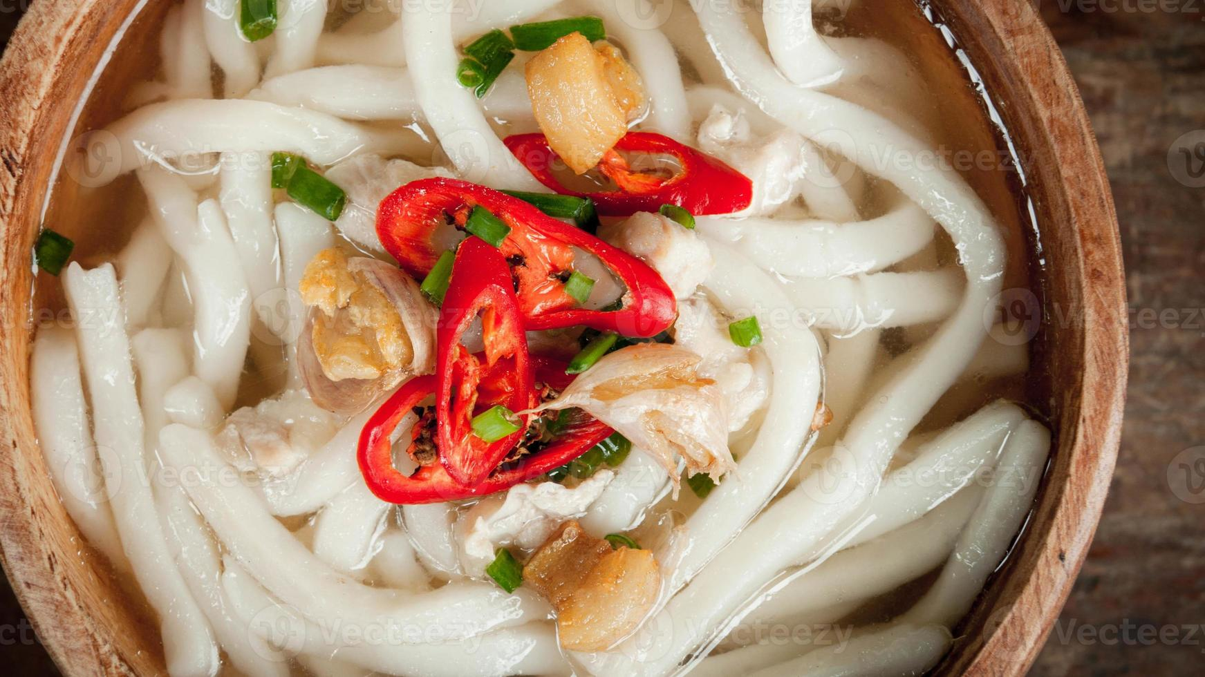 udon noodle in wood bowl on wooden floor background photo