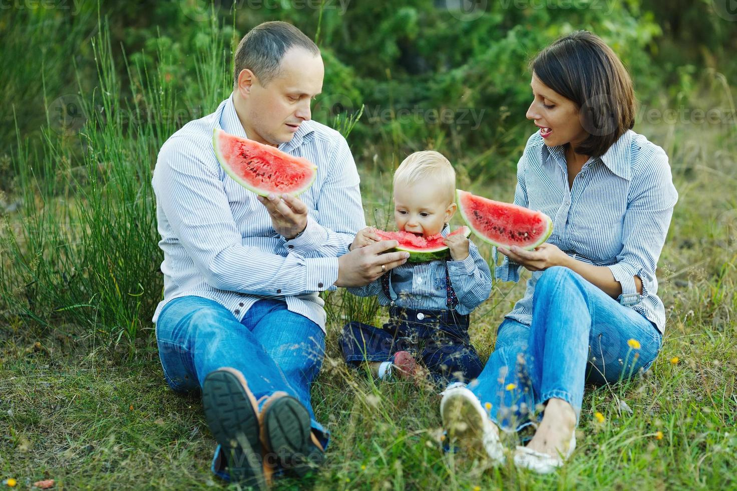 family eating watermelon photo