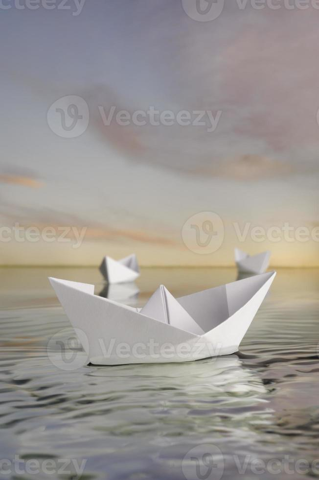 Three paper boats in calm water . photo