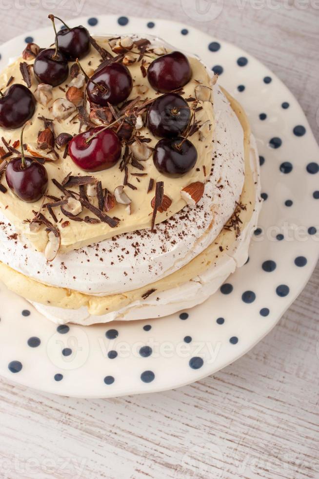 Pavlova cake with fresh cherry on the ceramic plate vertical photo