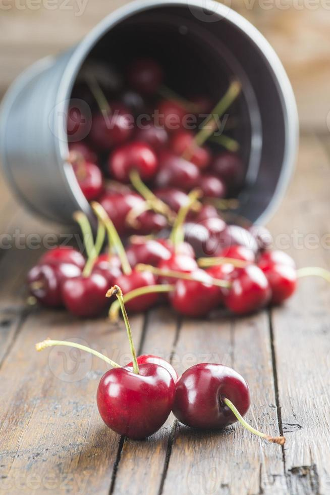 Little brass bucket of cherries on a table photo