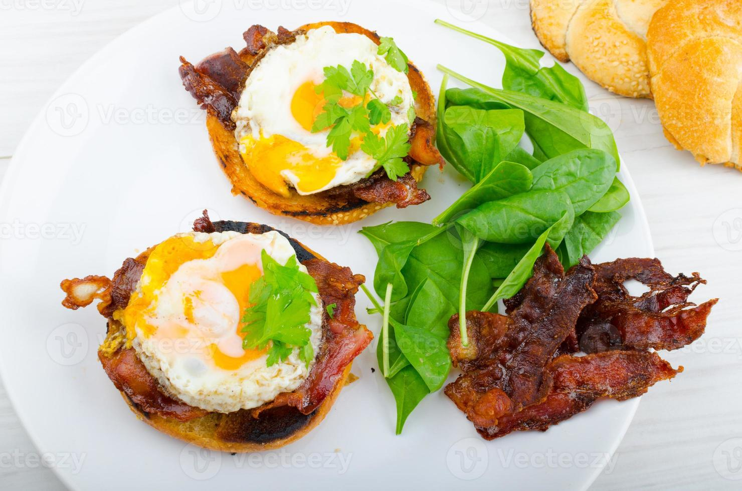 Eggs benedict with bacon and spinach photo