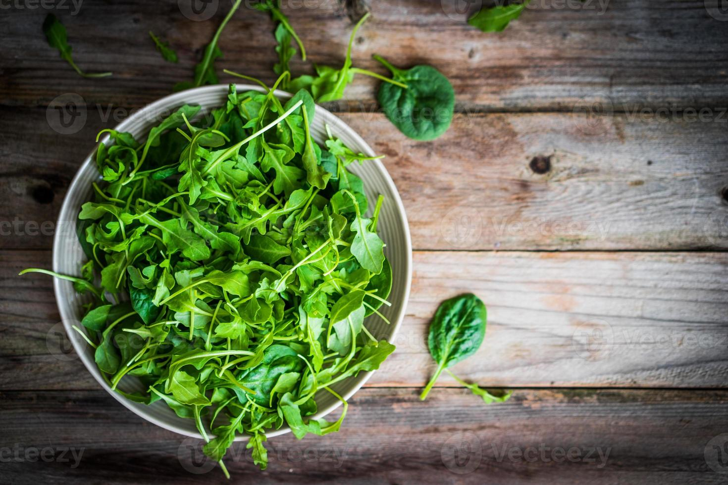 Fresh arugula and spinach salad on rustic background photo