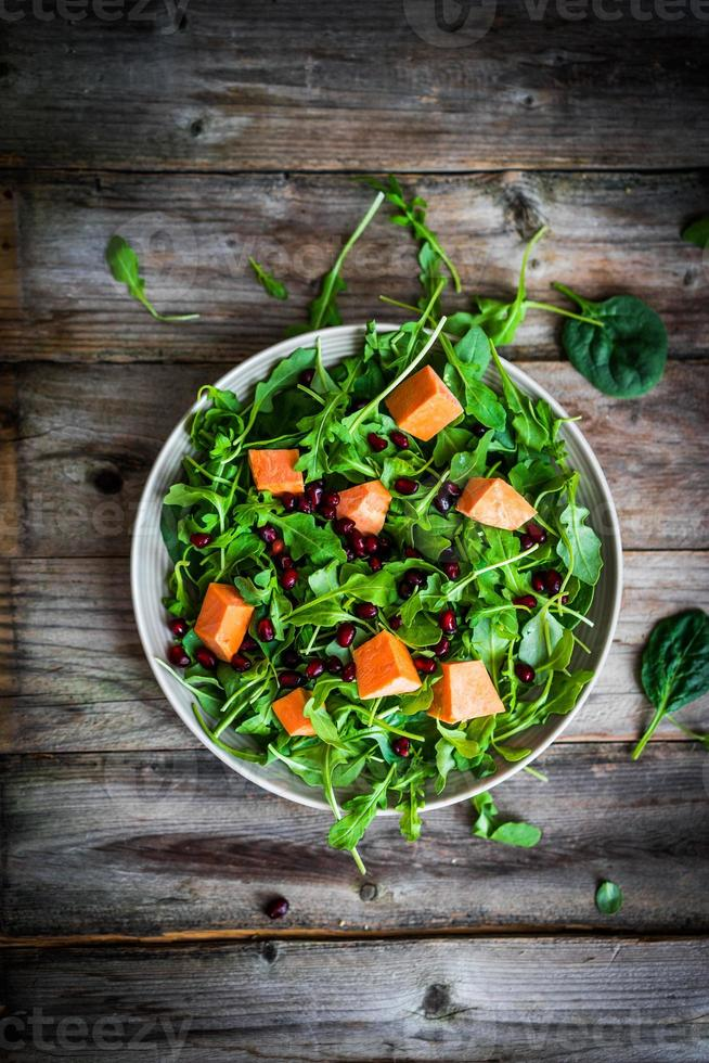 Fresh arugula and spinach salad with pumpkin on rustic backgroun photo