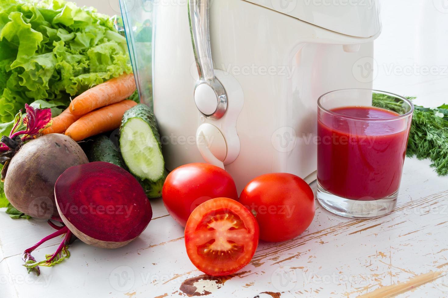 Selección de verduras y jugo de remolacha, fondo de madera blanca foto