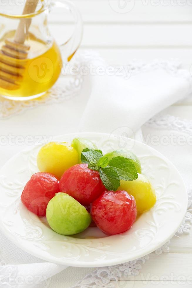 The dessert salad of watermelon and cantaloupe with honey. photo