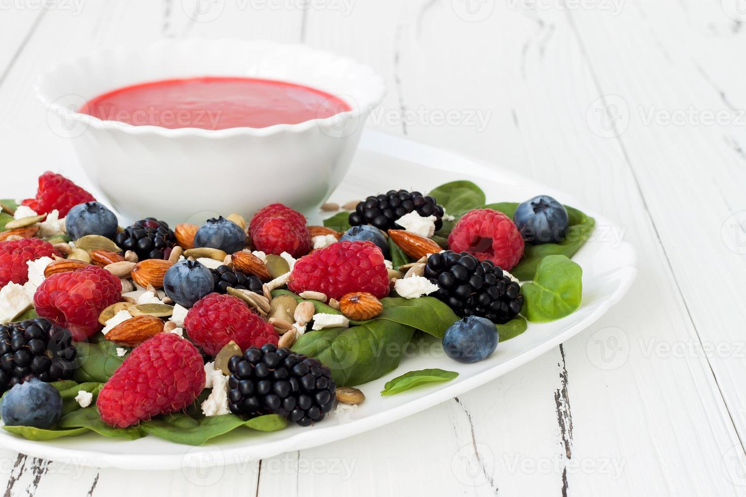 Mixed berry salad with almonds, feta cheese and raspberry vinaigrette photo