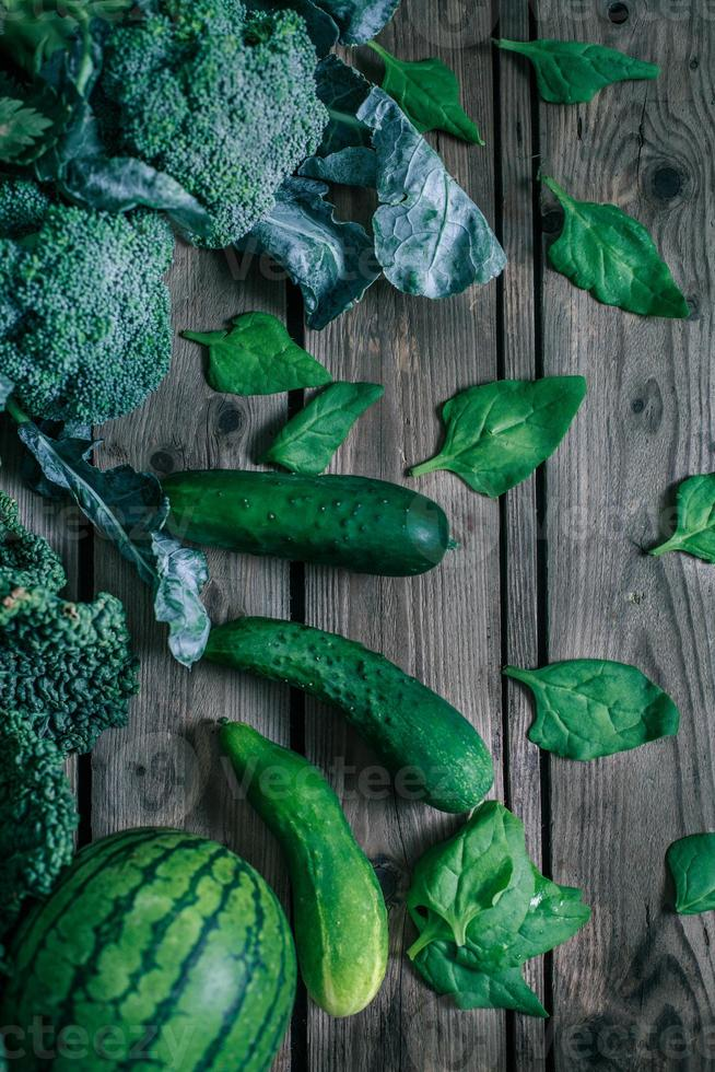 Various green vegetables on wooden table photo