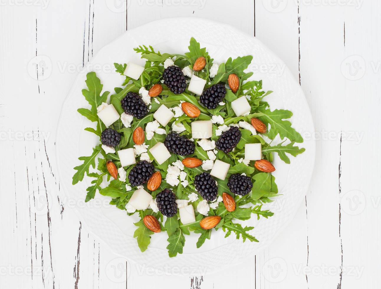 Green salad with arugula, melon, blackberries, almonds and feta cheese photo