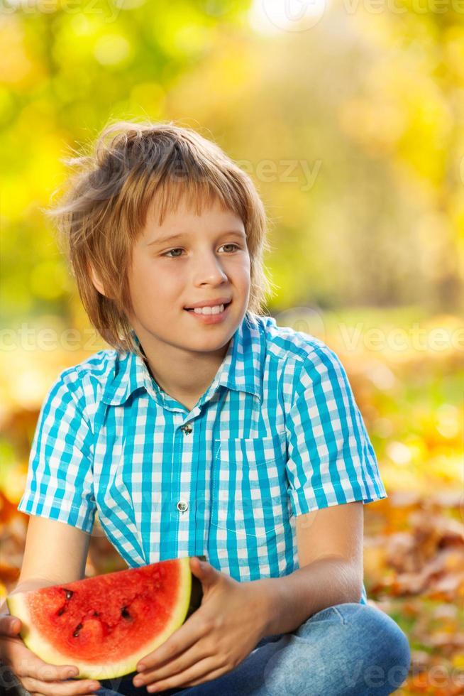 Retrato de niño con sandía en hojas foto