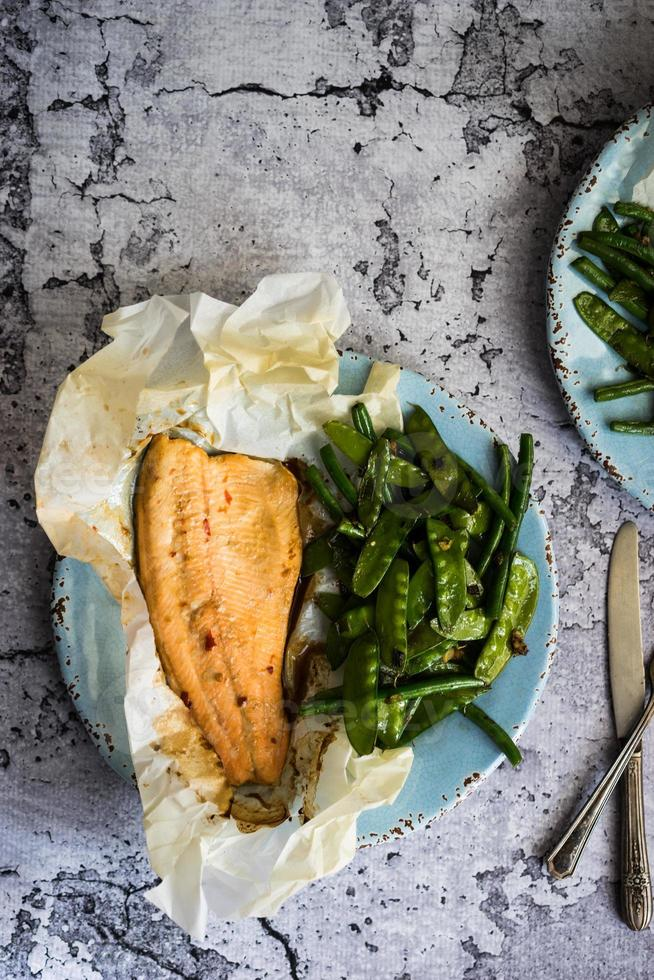 Baked fish with beans on rustic background photo