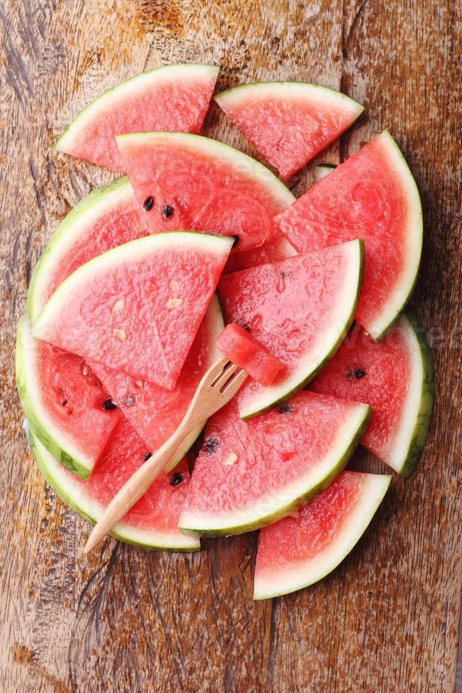 Slice of fresh watermelon on wooden background photo