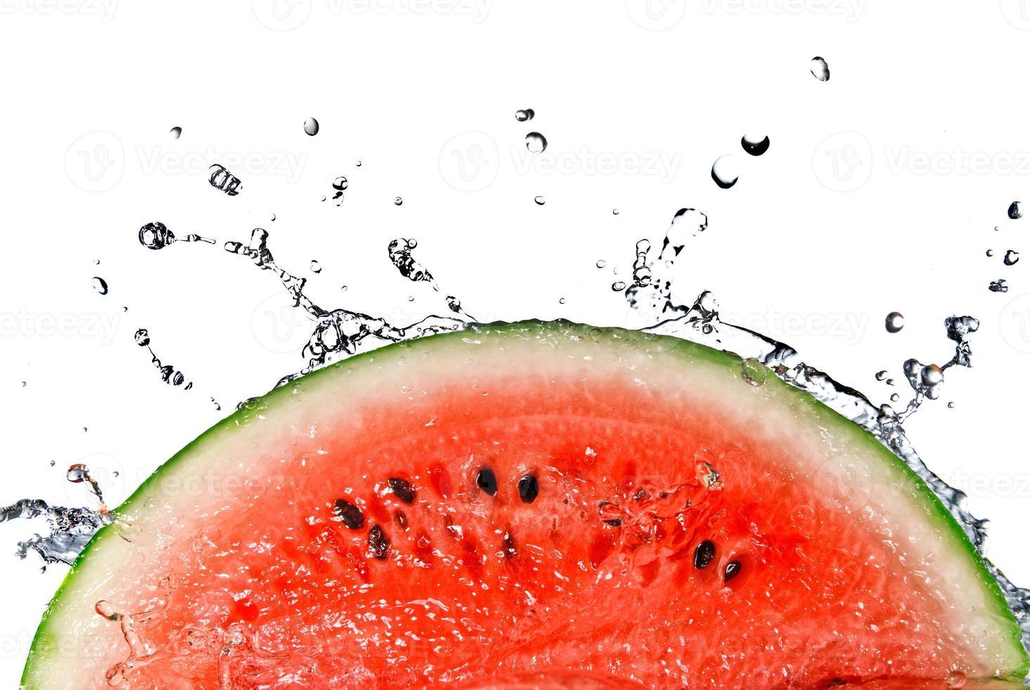 Slice of watermelon splashing into water photo