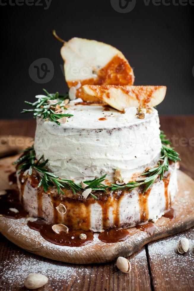 Tarta de crema con pera y decoración en la mesa foto