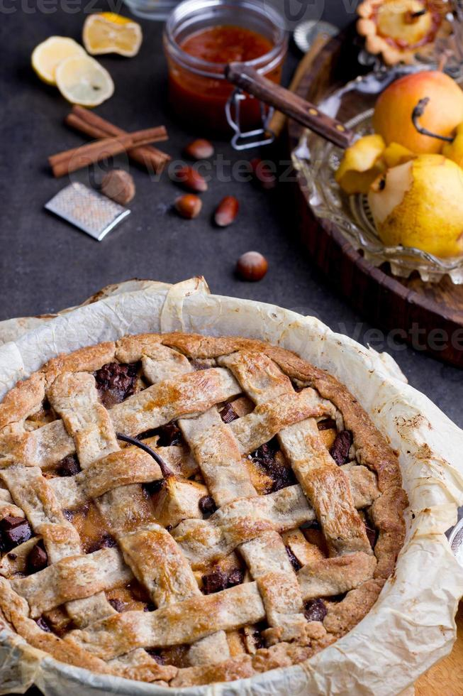 Apple/pear pie in a baking pan, with ingredients. photo