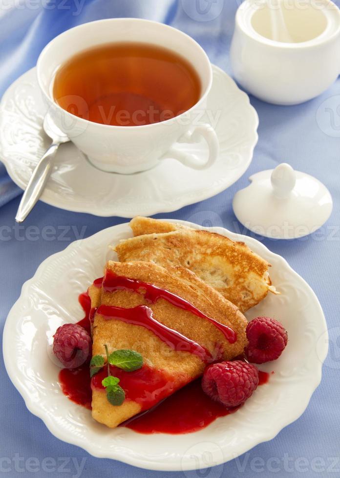 deliciosos panqueques con fresas y salsa de frambuesa. foto