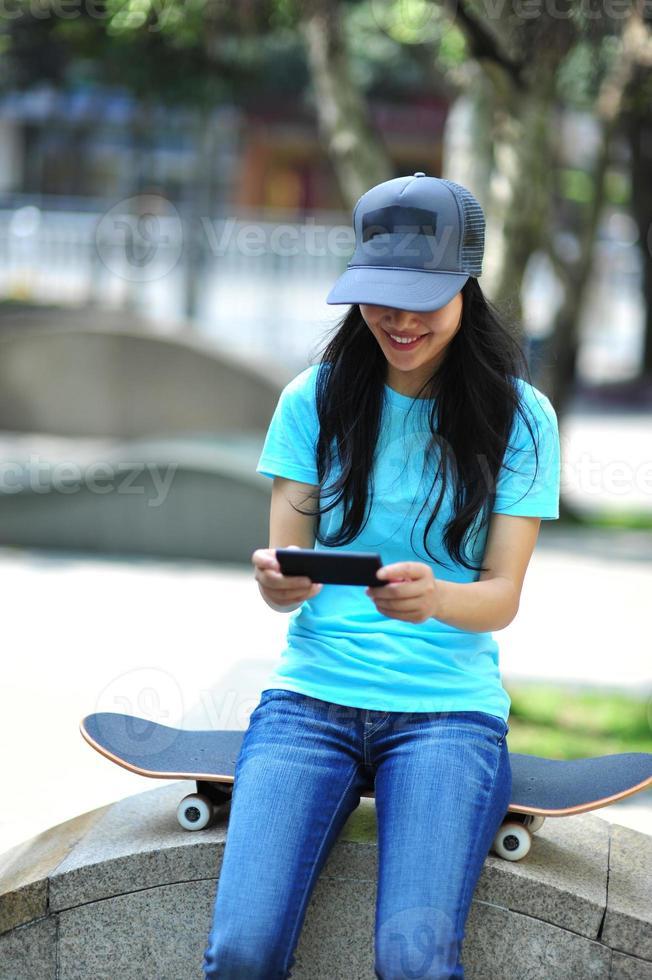 skater joven usa su teléfono celular foto