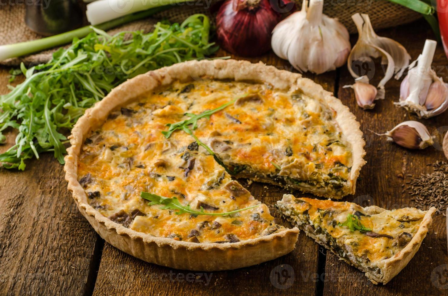 uma quiche de queijo com frango, rúcula e alho em uma mesa foto
