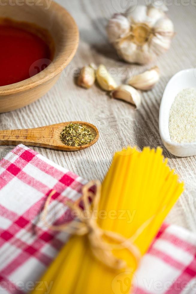 Spaghetti and other ingredients, parmesan, oregano on kitchen table photo