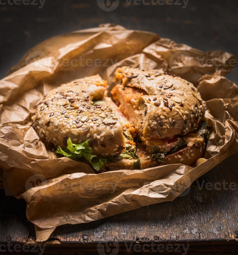 bun with chicken, cheese  lettuce  crumpled paper  rustic wooden background photo
