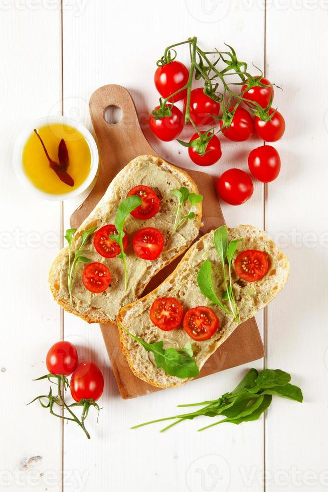 sandwich with cherry tomatoes and cream of avocado and arugula photo