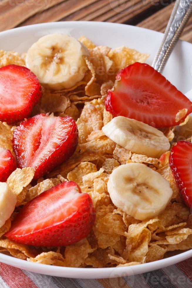 Breakfast muesli with strawberries and banana closeup vertical photo