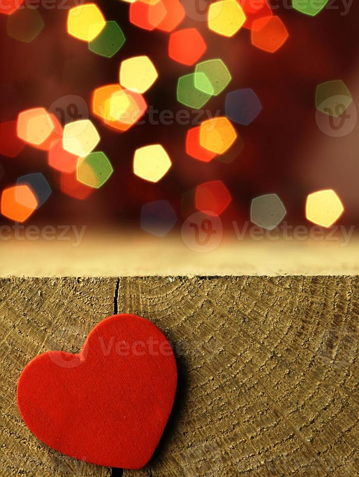 Red heart on the edge of a wooden table. photo