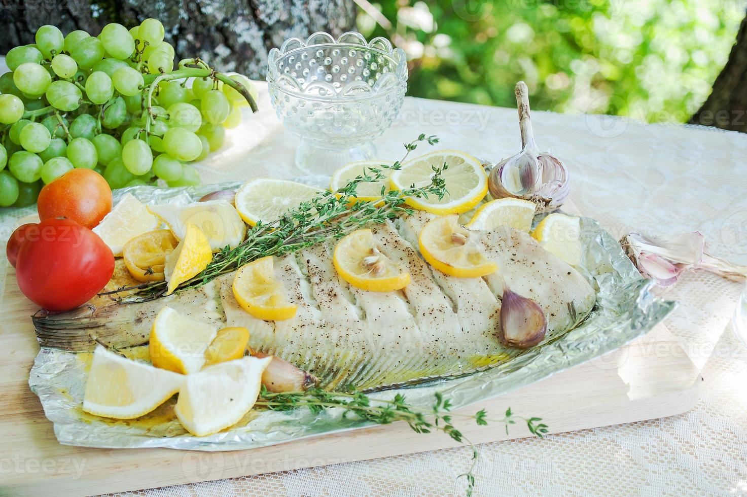 Lunch with fish flounder in Mediterranean style outdoors photo