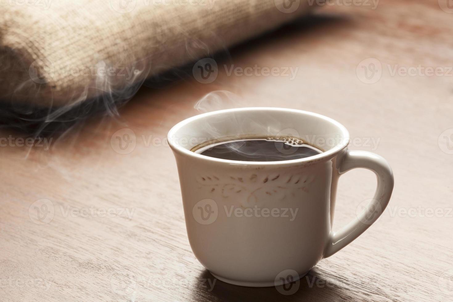 xícara branca em mesa de madeira photo