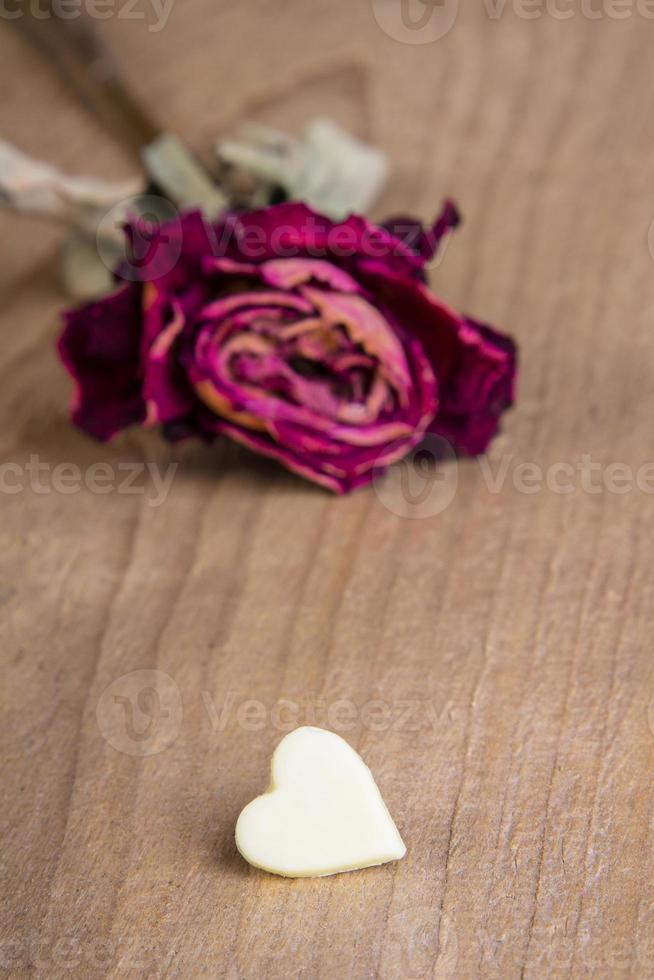 dried red rose and chocolate heart photo