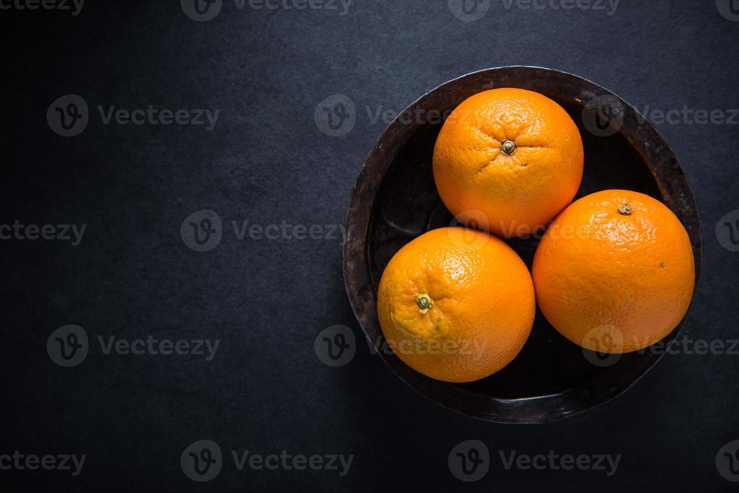 Cultivar fruta fresca de naranja en un tazón rústico foto