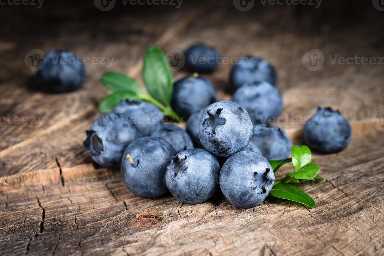 Blueberry with leaves on wooden background photo